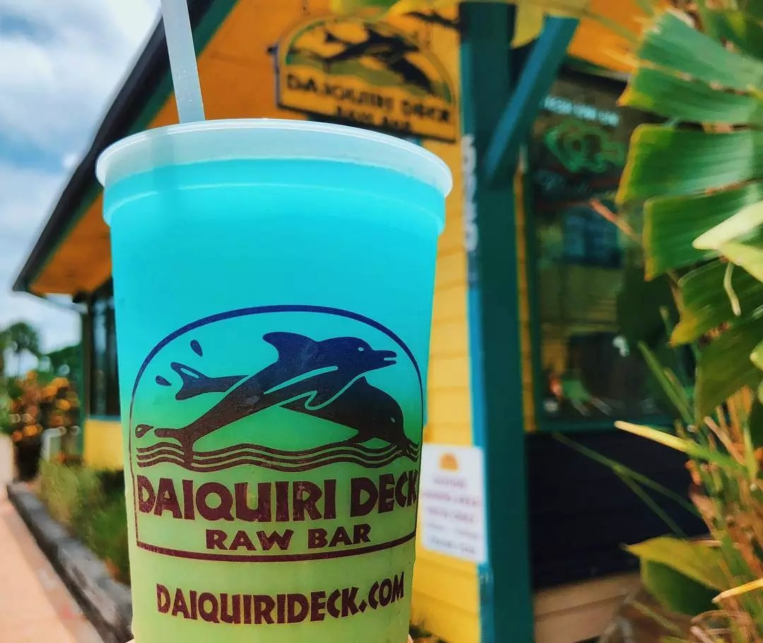 Closeup of blue and green rum drink with Daiquiri Deck Raw Bar building in background Photo by Instagram user @daiquierideck