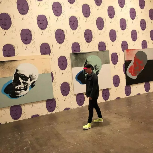 Man walks through Andy Warhol museum as 3 different paintings hang from the wall covered in wallpaper. Photo by Instagram user @johngeiger_