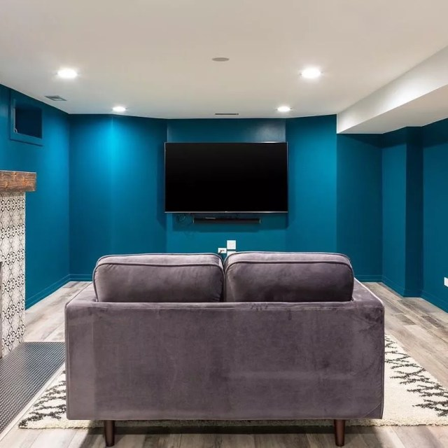 Basement Painted with Bright Blue Walls and a TV Hung on the Wall. Photo by Instagram user @magdainteriors