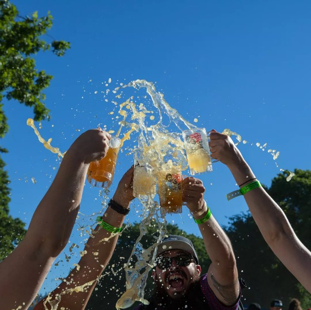 Beer splashing out of steins after enthusastic cheers by a group of people Photo by @oregonbrewfest