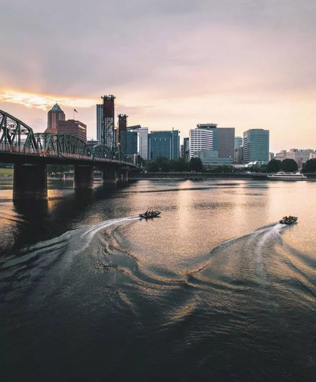 View of Willamette River with two boats in the water and Portland skyline in the background Photo by Instagram user @portland