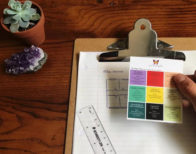Person holding bagua energy feng shui map while planning home design. Photo by Instagram user @jessneary.fengshui