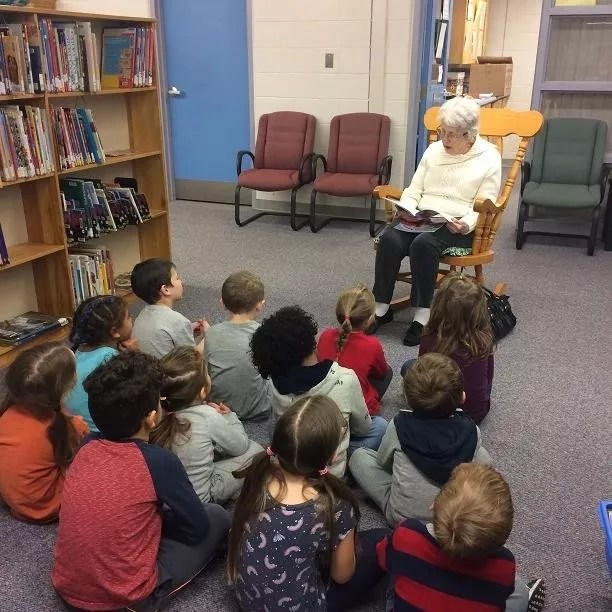 Elderly Woman Reading to Elementary Students. Photo by Instagram user @allseniorscarelivingcentres