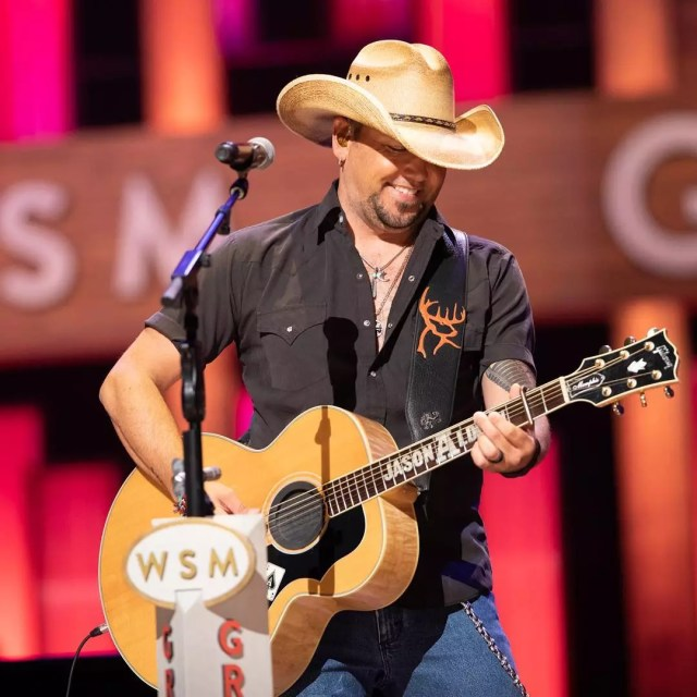Country singer Jason Aldean playing his guitar in front of a microphone. Photo by Instagram user @opry