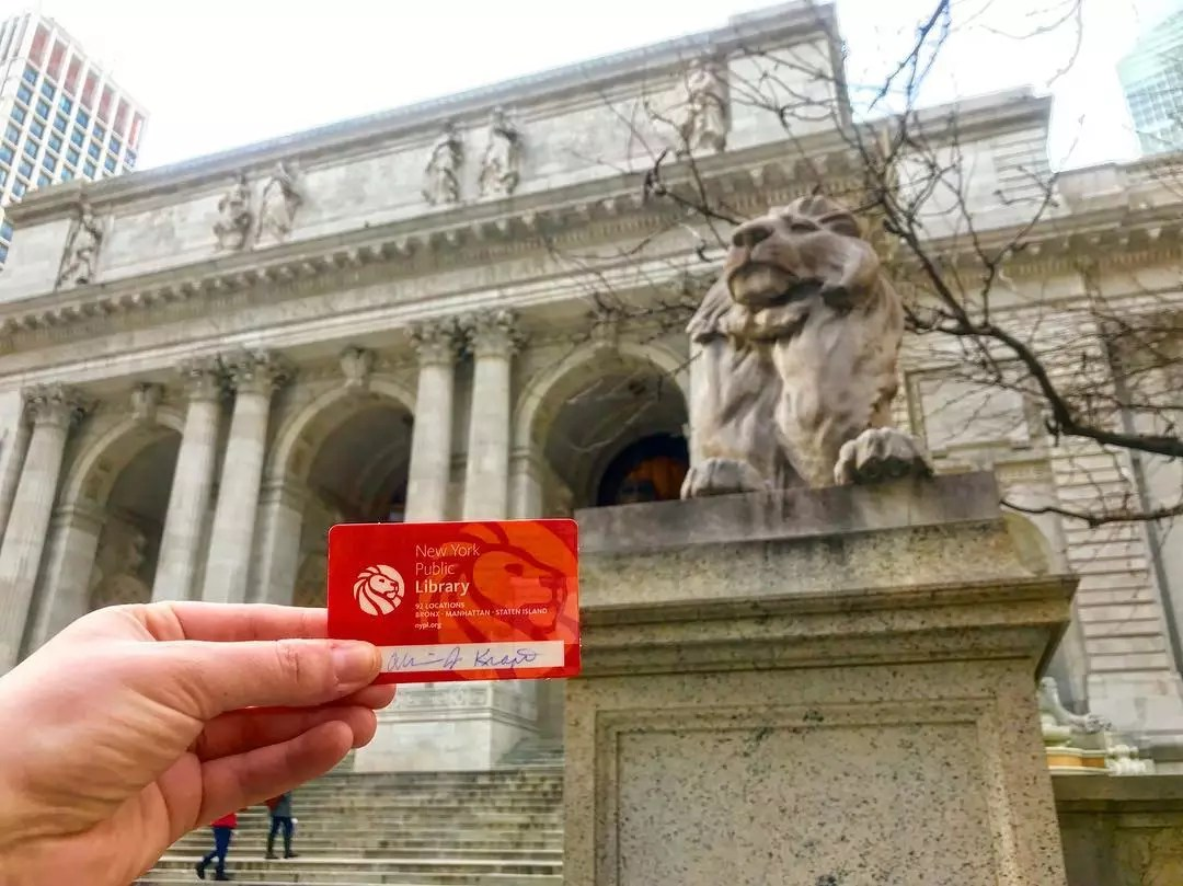 Person Holding Up Library Card in Front of the New York Public Library. Photo by Instagram user @ajkrafty