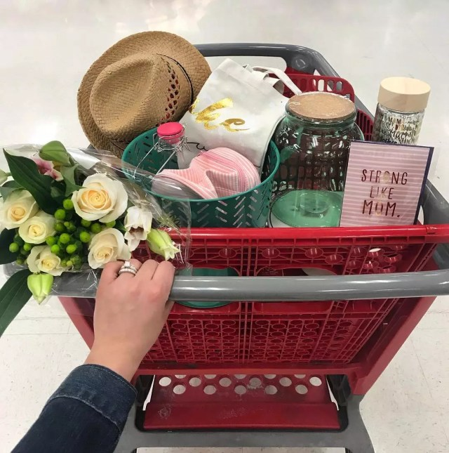 Person Pushing Shopping Cart Filled with Flowers, Hats, Jars, and Other Knick Knacks. Photo by Instagram user @mrs.tayflowers