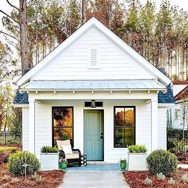 White Cottage with Blue Front Door and Rocking Chair on Front Porch. Photo by Instagram user @lyndsy.wojtus.realtor