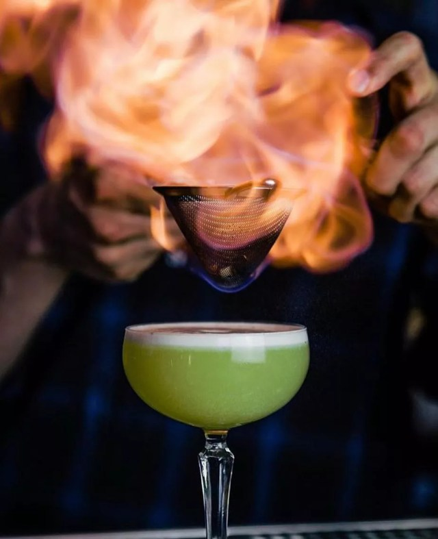 A bartender serves a green martini with fire on top. Photo by Instagram user @truststl