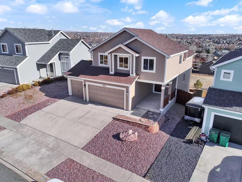 Aerial photo of two-story single family home with two garages and painted brown with white trim Photo by Instagram user @solidrockrealty
