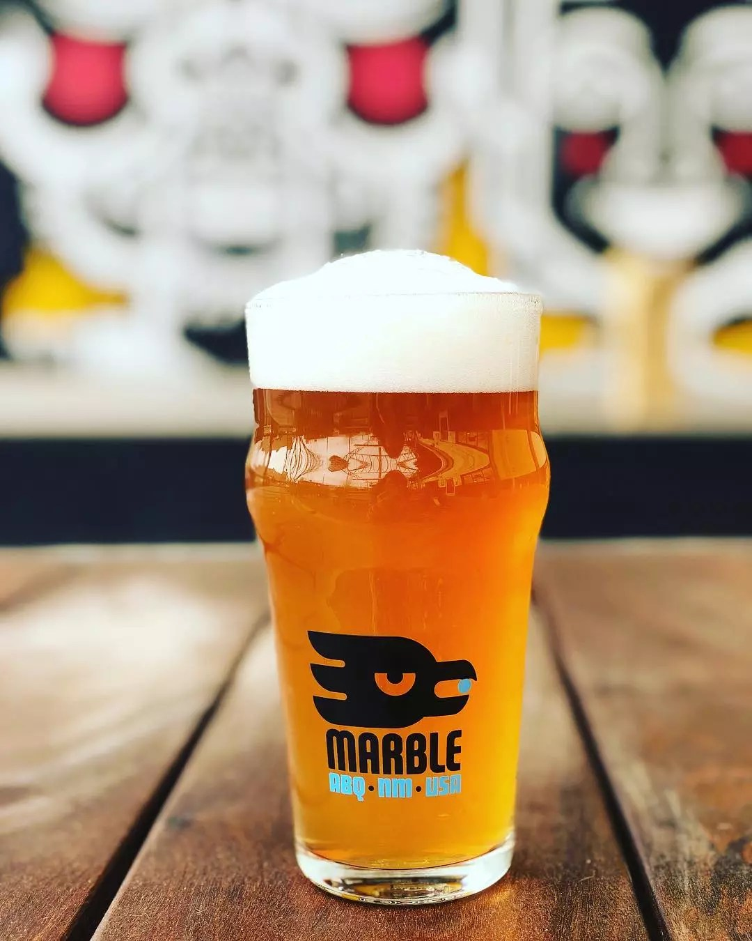 Closeup of pint of amber-colored beer with Marble Brewery logo on the glass. Photo by Instagram user @marblebrewery