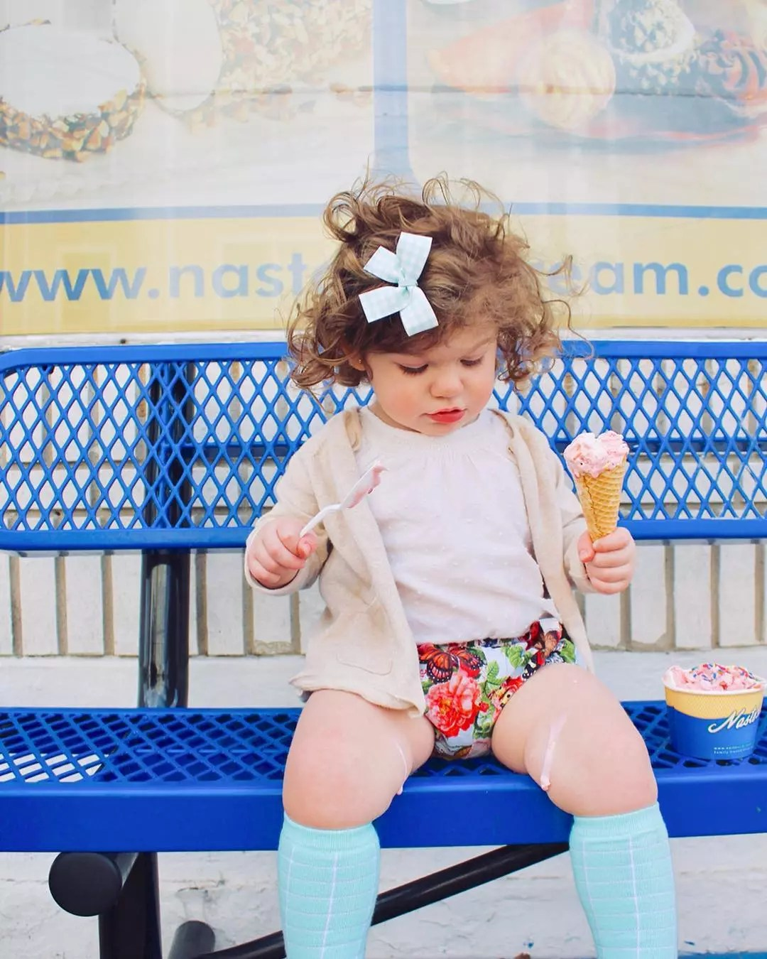Young girl looking at ice cream dripping on her leg while holding an ice cream cone and spoon. Photo by Instagram user @kathleen_templeton