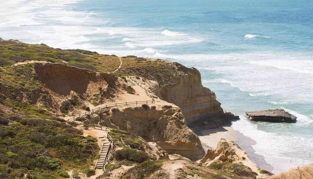 Looking at a tall cliff from above with a walkway along the side as ocean waves crash into the side. Photo by Instagram user @socallifemag