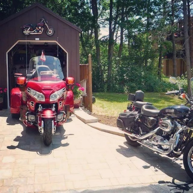 Red motorcycle being pulled out of a motorcycle shed photo by Instagram photo @northcountrysheds