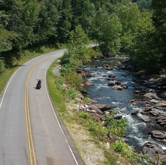 Aerial view of motorcycle on road next to river. Photo by Instagram user @officialtailofthedragon