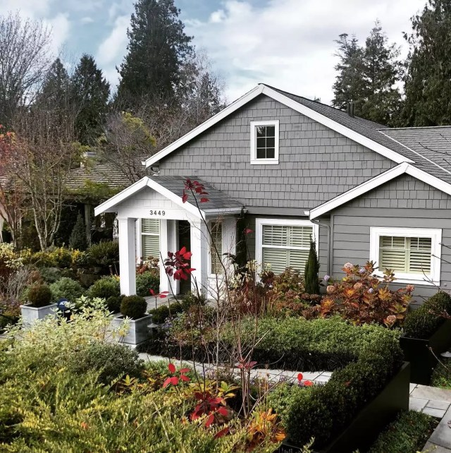 Grey Cape Cod style home with white pillars in Magnolia, Seattle. Photo by Instagram user @urbanjenni