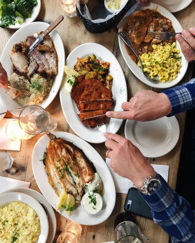 Hands cutting up German food at Suppenkusche. Photo by Instagram user @theculinaryedge