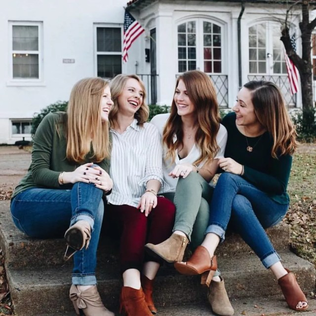 Four women sitting outside laughing. Photo by Instagram user @movingwiththemilitary