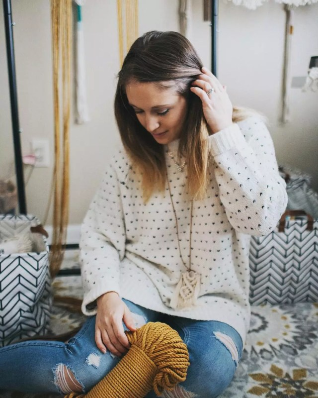 Woman sitting with totes of yarn. Photo by Instagram user @deserthomestudio