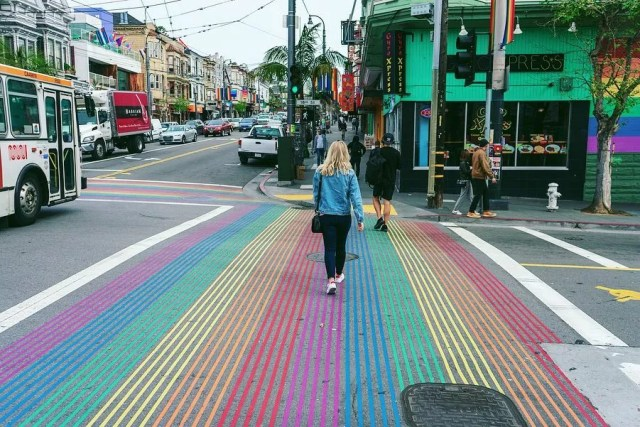 Woman walking across rainbow path on street in Castro District. Photo by Instagram user @stephpatullo