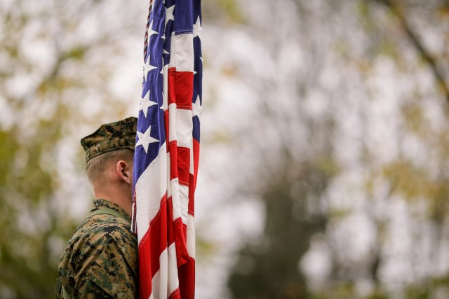 Man in military uniform standing behind US flag