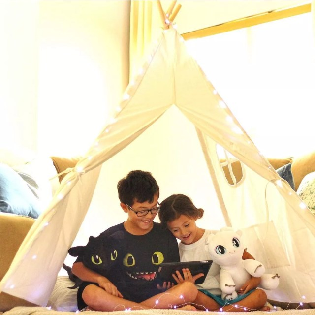 Little boy and girl reading a book in a fort.