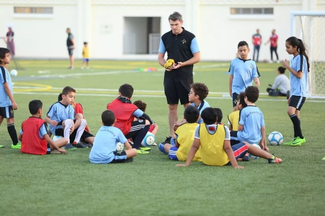 A group of kids sitting around for soccer practice. Photo by Instagram user @starfootballacademy