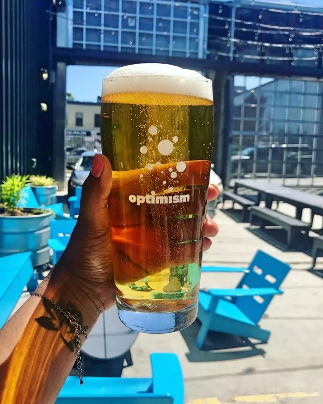 A hand holding a glass of beer from Optimism brewing. Photo by Instagram user @optimismbrewing