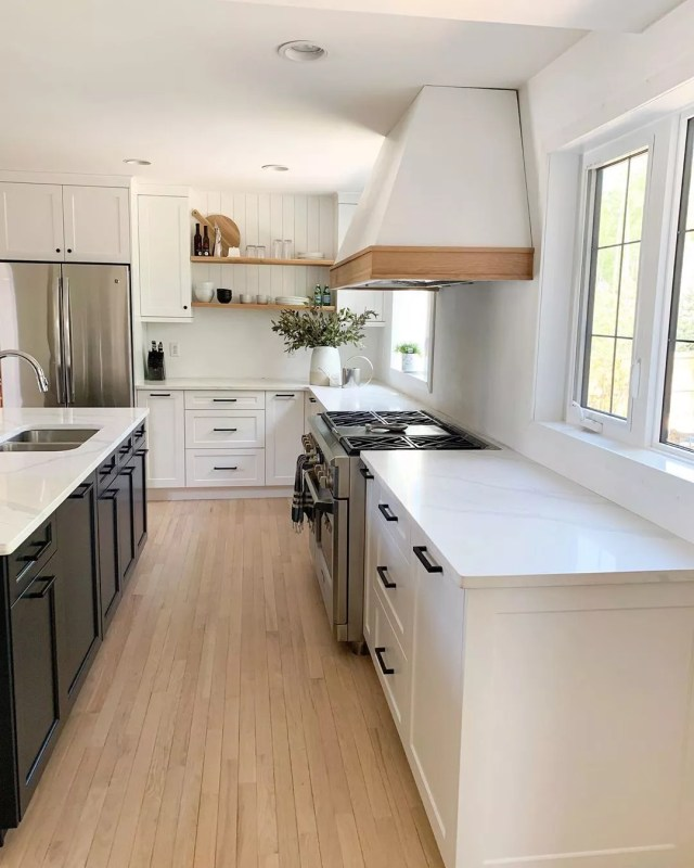 All white kitchen with black appliances and cabinets in a famrhouse design. Photo by Instagram user @jessicadevlindesign