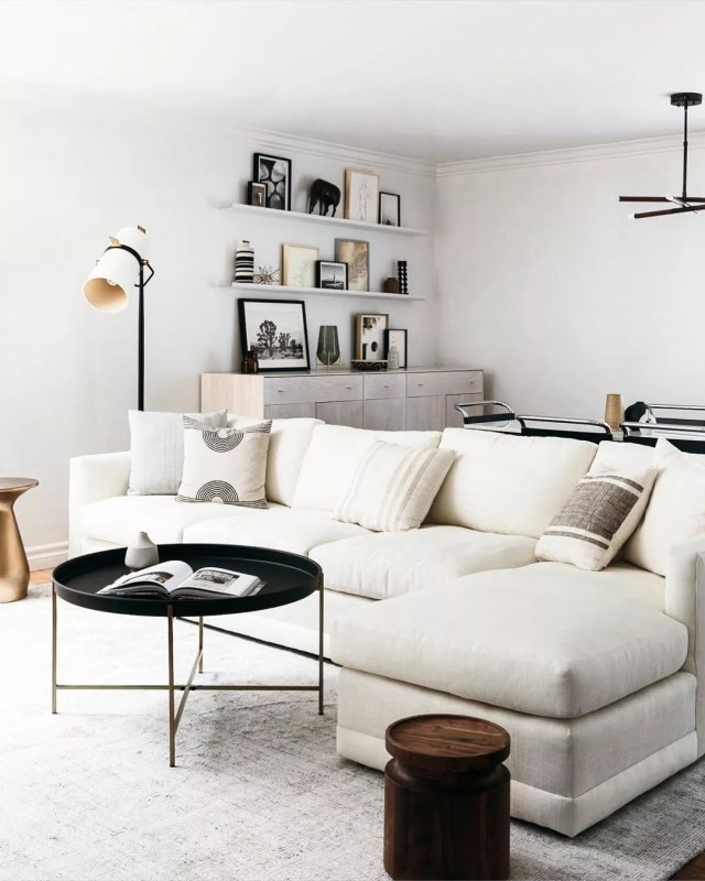 Living designed in Minimalist style with a tan couch and white walls and blush pillows. Photo by Instagram user @mi_property_solutions