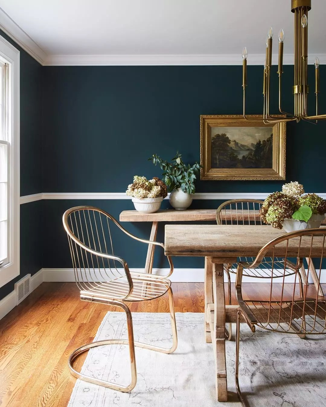 Dining room painted in forest green color with wood table and chairs. Photo by Instagram user @leannefordinteriors