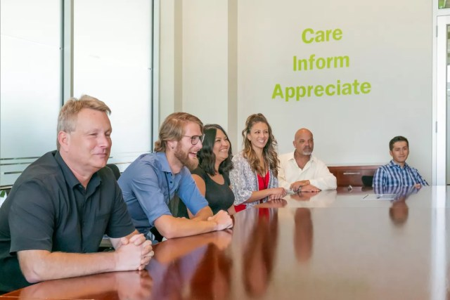 Employees at Extra Space Storage gather around conference room table