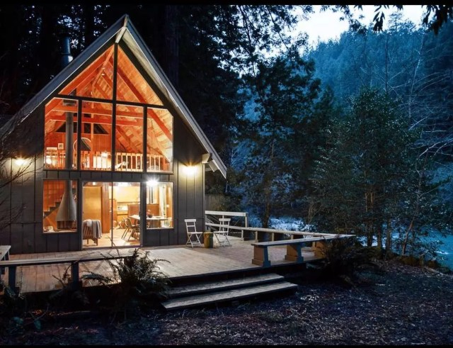 A-frame cabin in California at night. Photo by Instagram user @cozycabingetaways