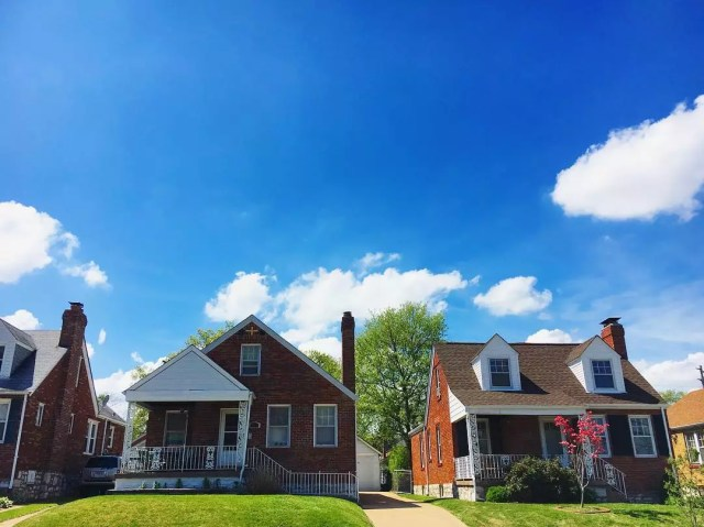 Two brick houses under a blue sky in Franz Park, St. Louis. Photo by Instagram user @emily_m_wasserman