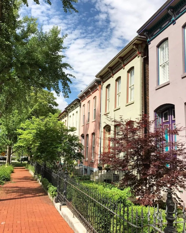 Purple, yellow, and pink rowhouses on a sunny day in Lafayette Square, St. Louis. Photo by Instagram user @yourcoachmeg