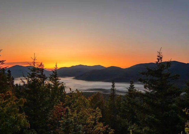 Tall green trees and mountains during sunset at Adirondack Park, NY. Photo by Instagram user @patbly