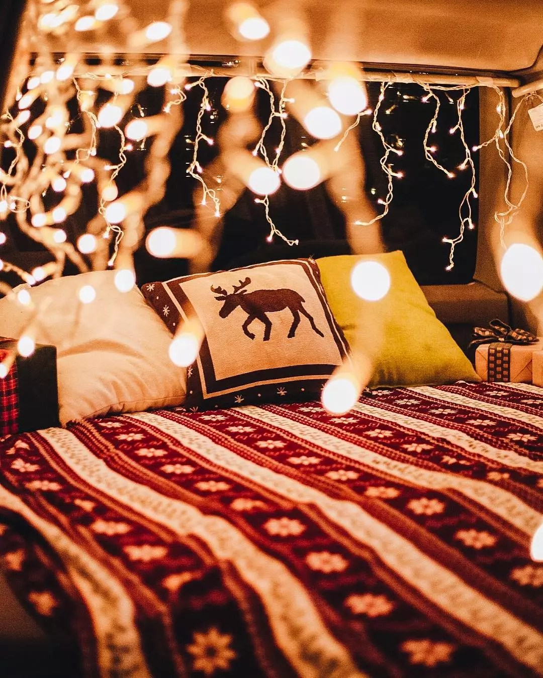 White twinkle lights in the back of van with bed and pillows