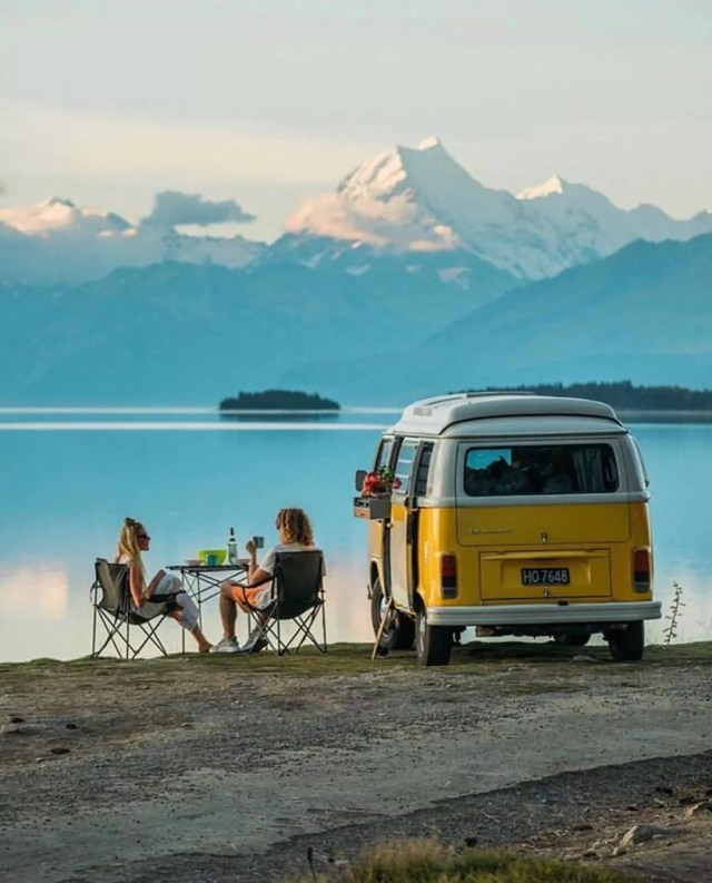 Two people sitting in chairs outside of their yellow van by the mountains. Photo by Instagram user @vanlife.living