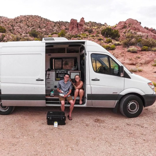 Couple sitting out of the side of their white sprinter van. Photo by Instagram user @simplholistic