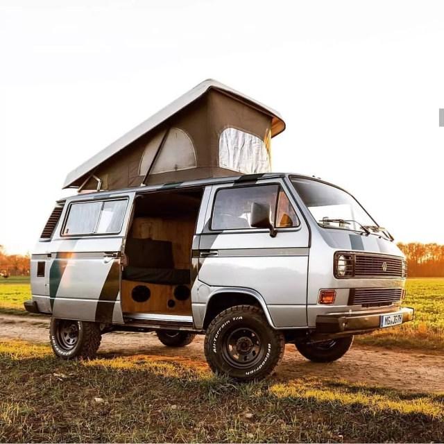 A Vanagon van with an open door in a field. Photo by Instagram user @vwt3spain