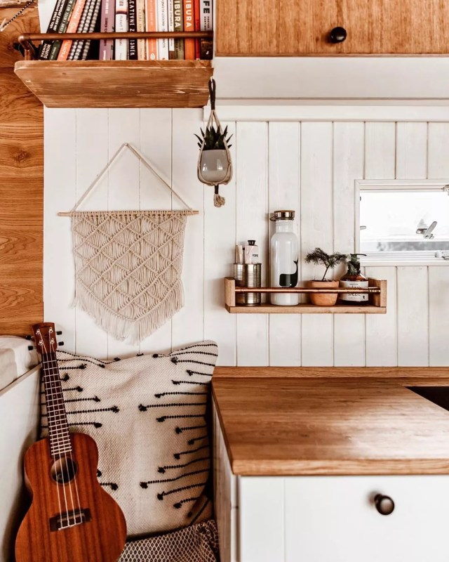 White wood walls with brown shelf. Photo by Instagram user @nomathehappyvan