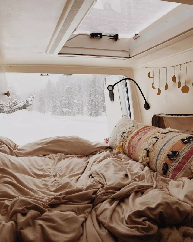 Van bed with a snow storm in the background. Photo by Instagram user @dynamoultima