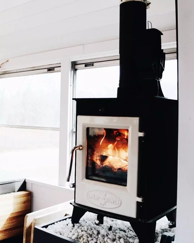 Black wood burning stove in a van. Photo by Instagram user @trebventure