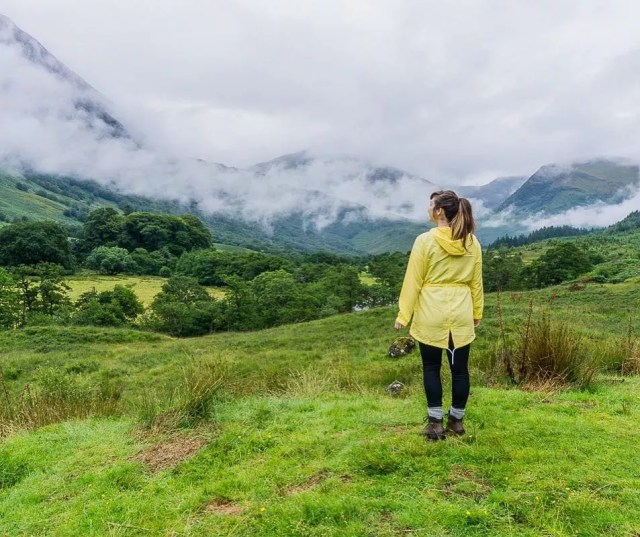 Girl in yellow jacket staring at mountains