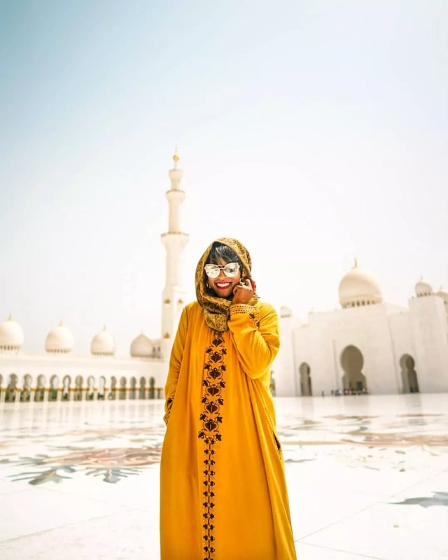 Girl in yellow sari in front of a mosque. Photo by Instagram user @glographics