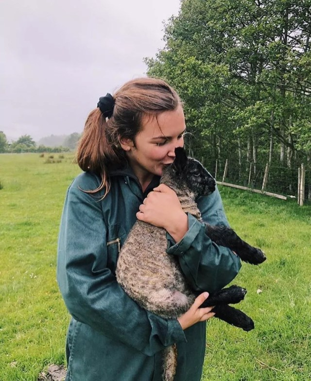 Young woman holding a black-faced lamb. Photo by Instagram user @johannaa.mariiee
