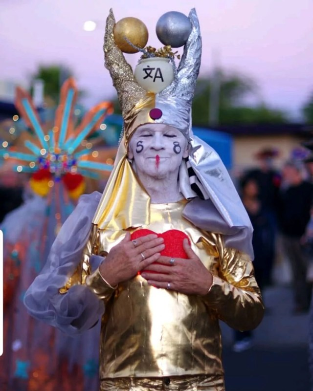 Man dressed in white and gold holding a heart for a festival. Photo by Instagram user @allsoulsprocessiontucson