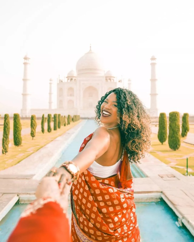 Influencer holding hands with man in front of Taj Mahal. Photo by Instagram user @glographics