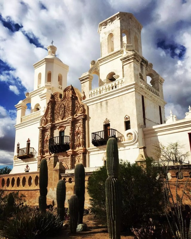 White Mission San Xavier del Bac with cacti in front of it. Photo by Instagram user @morgan_lorraine_