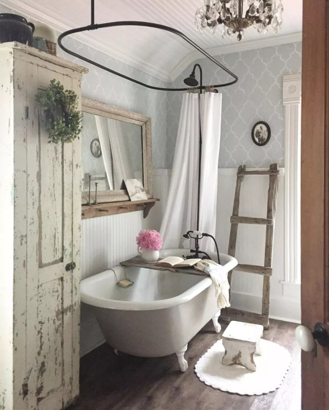 Rustic bathroom with blue wallpaper and big tub. Photo by Instagram user @bryartonfarm