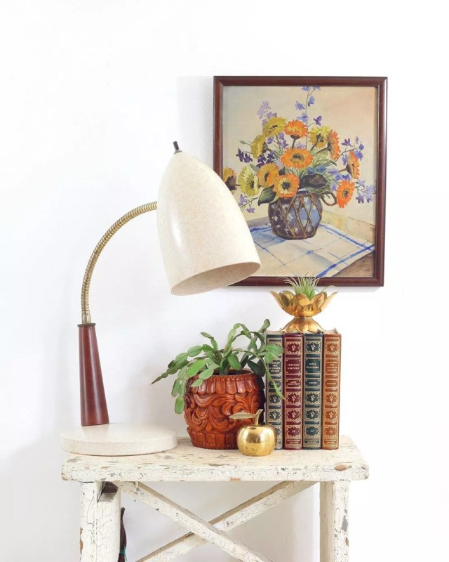 White vintage table with books and lamp on it. Photo by Instagram use @wiseapplevintage